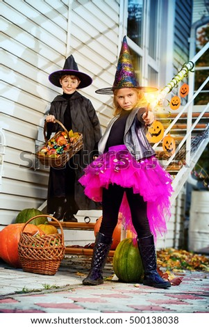 Happy children in a costumes of witches and wizards celebrating halloween. Trick or treat. Halloween party. #500138038