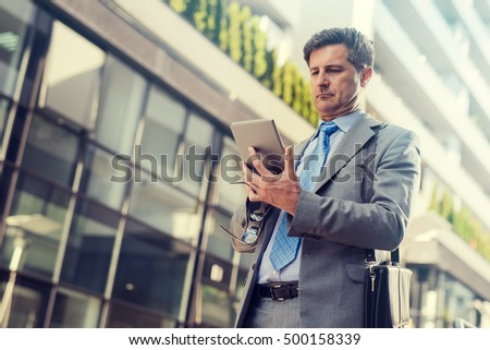 Close up portrait of a successful businessman using a digital tablet while standing by a modern office building. #500158339