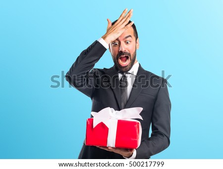 Businessman holding a gift over colorful backgound #500217799