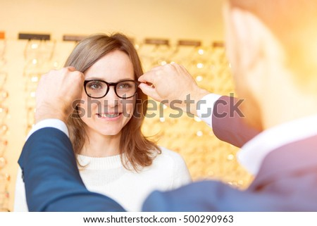View of a Young attractive  woman testing new glasses with optician #500290963