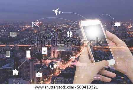 Double exposure of woman hand using mobile smart phone and city night buildings with internet wifi icons, web icons connection, internet of things concept . #500410321