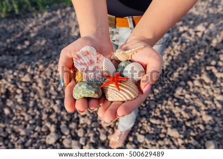 Close up shot of woman's hands holding seashells and starfish #500629489