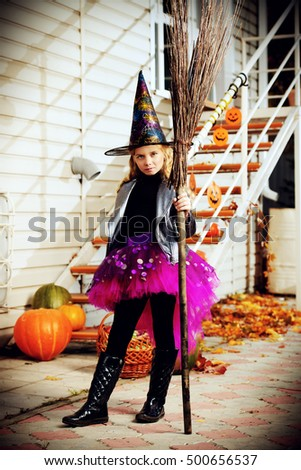 Pretty little girl in a costume of witch with her magic broom celebrating halloween. Trick or treat. Halloween party. #500656537