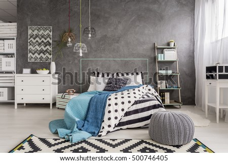 Cropped shot of a comfortable interior with grey walls and black and white rug #500746405
