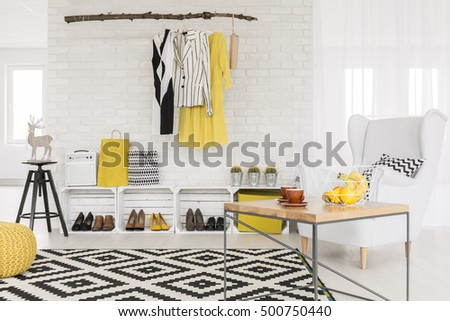 White interior with yellow and black details and simple furniture #500750440