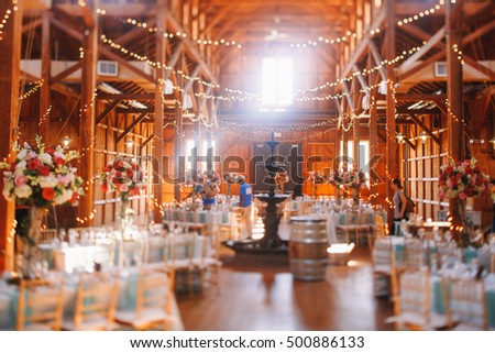 Sun shines over the bronze fountain standing in the middle of wooden hagar prepared for a wedding dinner #500886133