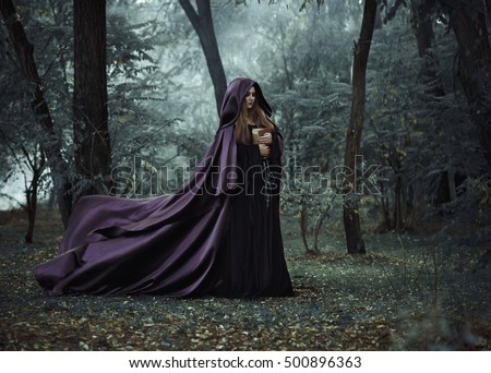 Halloween witch hold old book vintage style. Gothic dress purple hood cape long train fly flutter wind. mystical power woman. Fantasy dark nature forest black tree Fashion medieval clothes costume Royalty-Free Stock Photo #500896363