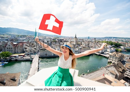 Young female tourist with swiss flag on the top of the tower in Zurich city. Woman having a great vacation in Switzerland #500900941