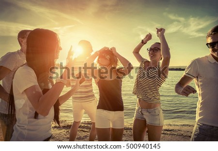 Friends funny dance on the beach under sunset sunlight. #500940145