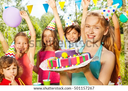 Portrait of smiling young girl holding B-day cake #501157267
