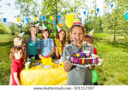 Smiling boy holding birthday cake with candle #501157387