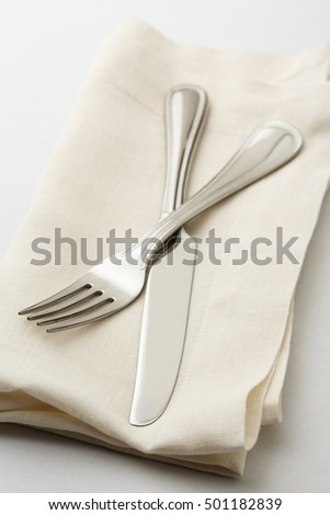 Simple, classic table setting place setting with fork and knife on white linen napkin. Selective focus on tines of fork. #501182839