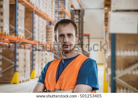 portrait of a smiling young warehouse worker working in a cash and carry wholesale store. #501253405