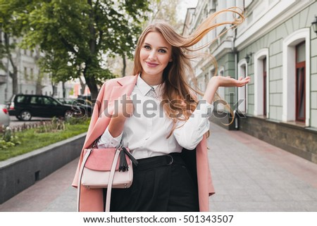 young stylish beautiful woman walking in street, wearing pink coat, purse, white shirt, black skirt, fashion outfit, autumn trend, smiling happy, accessories #501343507