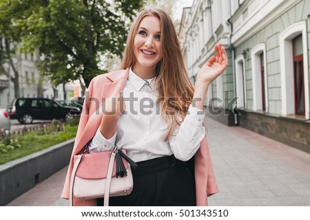 young stylish beautiful woman walking in street, wearing pink coat, purse, white shirt, black skirt, fashion outfit, autumn trend, smiling happy, accessories #501343510