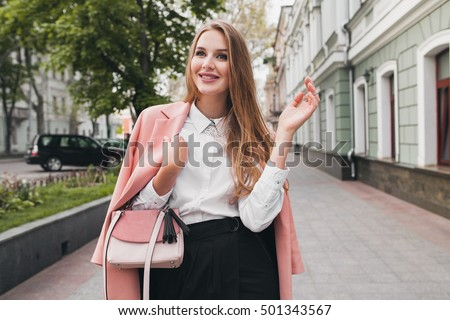young stylish beautiful woman walking in street, wearing pink coat, purse, white shirt, black skirt, fashion outfit, autumn trend, smiling happy, accessories #501343567