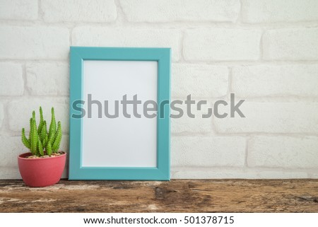 Blue photo frame on old wooden table with cactus over white brick wallpaper background