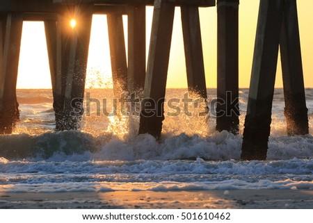 Sunset waves crashing on pier #501610462