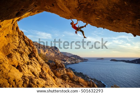 Male climber on overhanging rock against beautiful view of coast below Royalty-Free Stock Photo #501632293