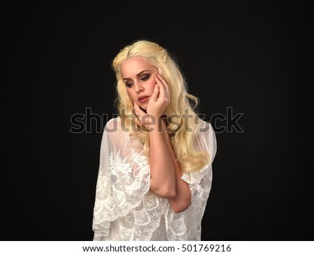 portrait of a beautiful woman with long blonde hair, wearing a white lace dress. isolated on a black background. #501769216
