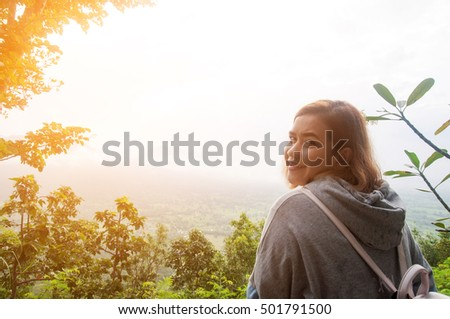 woman look at the mountain on view point in morning. Phu Thok Mountain at Chiang Khan ,Loei Province in Thailand. subject blurred and low key with wide angle lens #501791500