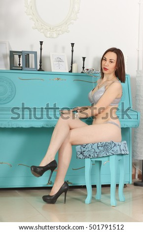 Attractive Nastya in lingerie sitting on a stool next to the turquoise piano #501791512
