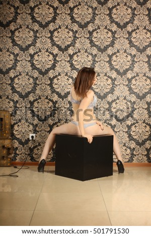 Attractive Nastya in lingerie sitting on a black cube, turning in the floor profile in the interior #501791530