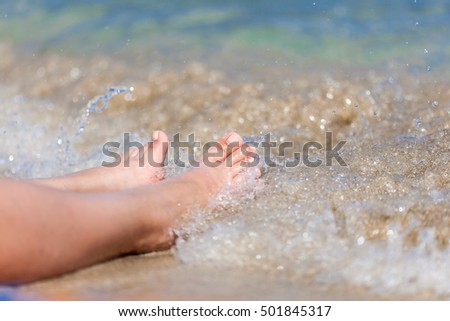 Legs of woman close-up on the beach in the water #501845317