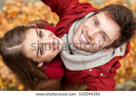 love, technology, relationship, family and people concept - close up of happy smiling young couple taking selfie in autumn park