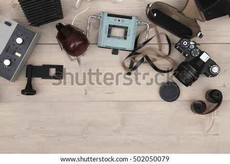 Old film camera and developer on wooden background