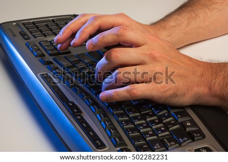 Close up low angle view of a man typing on a laptop computer in darkness conceptual #502282231