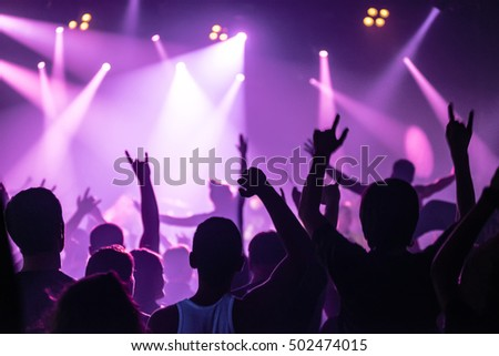 silhouettes of concert crowd in front of bright stage lights #502474015