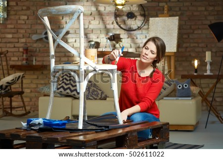 Diy woman painting, renewing chair at home. Royalty-Free Stock Photo #502611022
