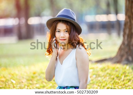 Happy asian woman speaking smartphone outdoor, asian beauty #502730209