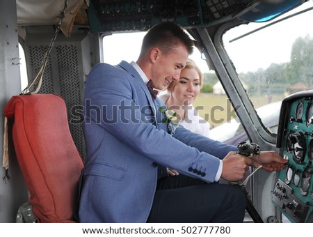 Happy wedding couple bride and groom riding helicopter. Closeup. #502777780