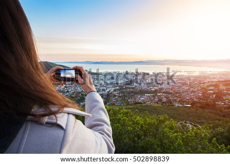 A female tourist taking a photo on her phone of the view of the city of Cape Town