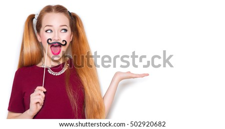 Beauty surprised funny teenage girl with paper mustache on stick showing empty copy space on the open hand palm for text, white background, presenting point. Proposing product. Advertisement gesture #502920682