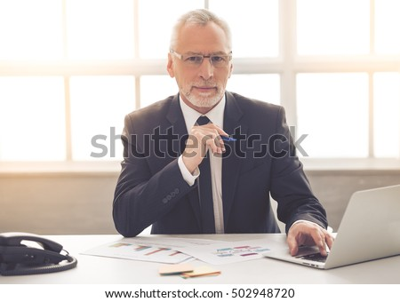 Handsome mature businessman in classic suit and eyeglasses is using a laptop and looking at camera while working in his office Royalty-Free Stock Photo #502948720
