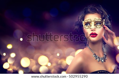 Beauty model woman wearing venetian masquerade carnival mask at party over holiday dark background with magic glow. Christmas and New Year celebration. Glamour lady with perfect make up and hairstyle #502955290