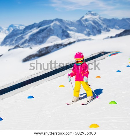 Child in alpine ski school with magic carpet lift and colorful training cones going downhill in the mountains on a sunny winter day. Little skier kid learning and exercising skiing on a slope. #502955308