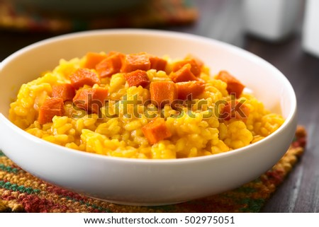 Pumpkin risotto prepared with pumpkin puree, roasted pumpkin pieces on top, photographed with natural light (Selective Focus, Focus in the middle of the image) #502975051