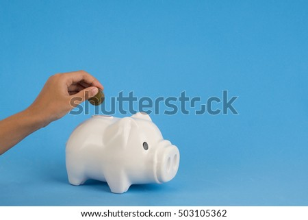 kids hand add coin to piggy bank save coin, time and money concept. copy space on right side. #503105362