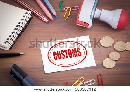 Customs stamp. Wooden office desk with stationery, money and a note pad