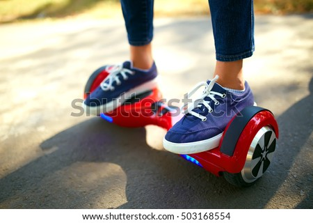 young man  riding on the Hoverboard in the park. content technologies. a new movement. Close Up of Dual Wheel Self Balancing Electric Skateboard Smart. on electrical scooter outdoors #503168554
