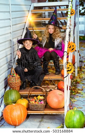 Happy children in a costumes of witches and wizards celebrating halloween. Trick or treat. Halloween party. #503168884