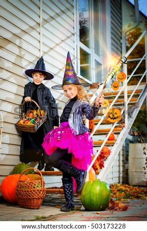Happy children in a costumes of witches and wizards celebrating halloween. Trick or treat. Halloween party. #503173228
