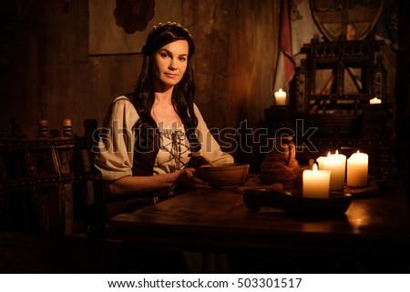 Medieval woman in ancient castle interior.