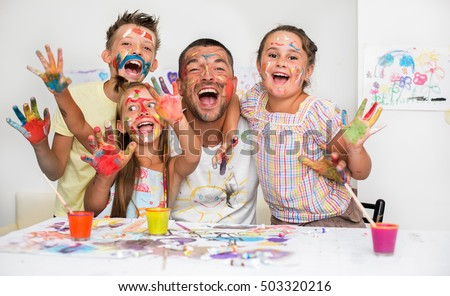 Portrait of a cute happy father with children painting and having fun. They are showing their hands painted in bright colors #503320216