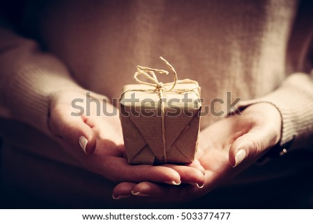 Giving a gift, handmade present wrapped in paper. Christmas time, vintage mood.