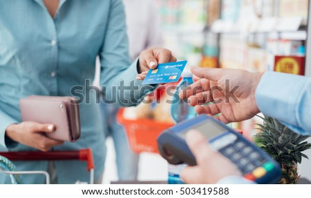 Woman at the supermarket checkout, she is paying using a credit card, shopping and retail concept Royalty-Free Stock Photo #503419588